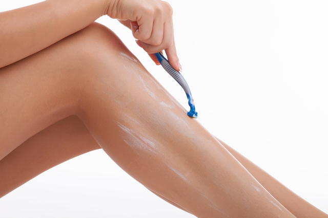 Close up of legs of healthy girl shaving it carefully. She has shaving cream on her legs. Isolated on background