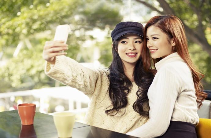 young friends taking selfie in coffee shop.