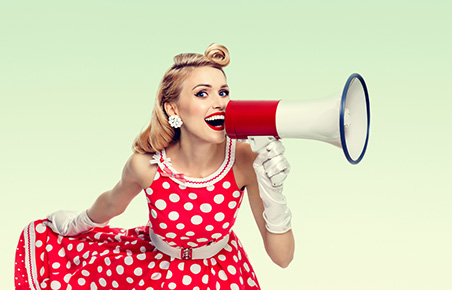 Woman holding megaphone, dressed in pin-up style red dress in polka dot, on green background. Caucasian blond model posing in retro fashion vintage studio shoot. Copyspace area for advertising slogan or text message.