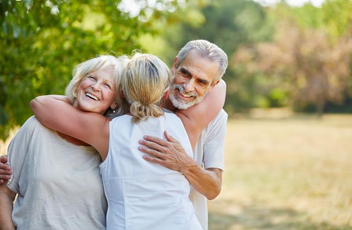 Glückliche Senioren als Freunde im Sommer im Garten umarmen sich