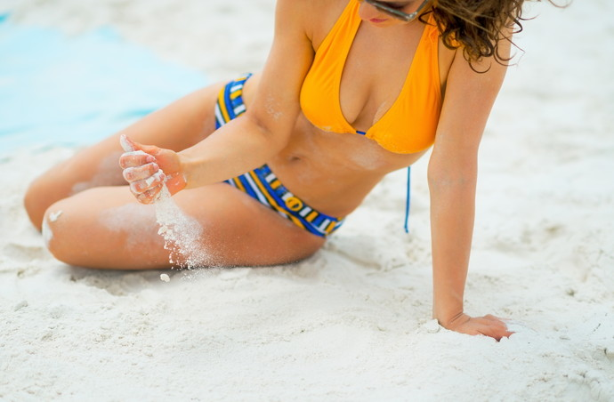 Closeup on young woman playing with sand on beach