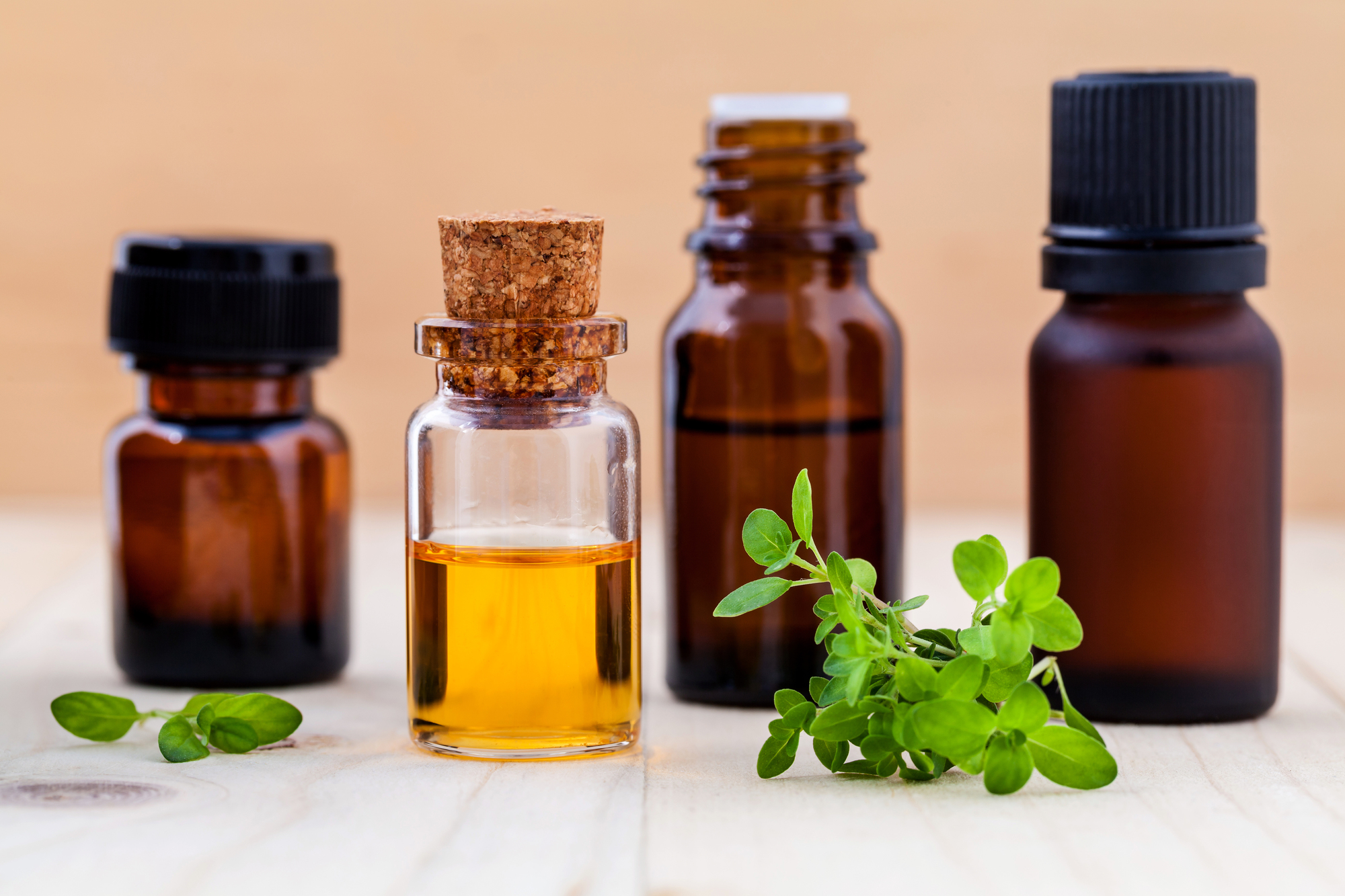 Fresh lemon thyme leaves and essential oil with shallow depth of field setup on wooden background .