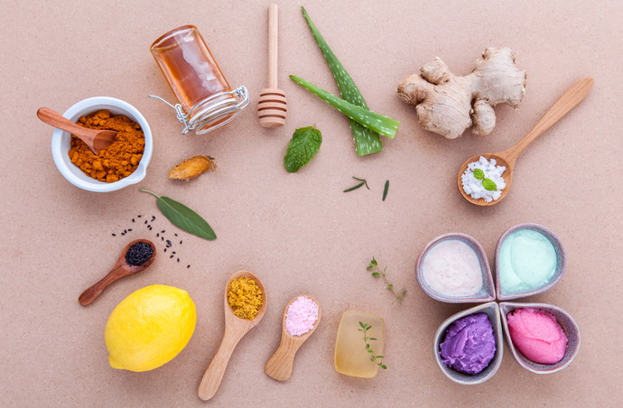 Alternative skin care and homemade scrubs with natural ingredients sage ,turmeric ,sea salt ,honey, aloe vera,lemon ,rosemary,mint and sesame set up on brown table.