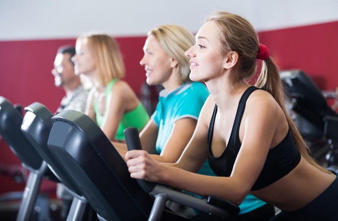 positive adults in gym working out at group class
