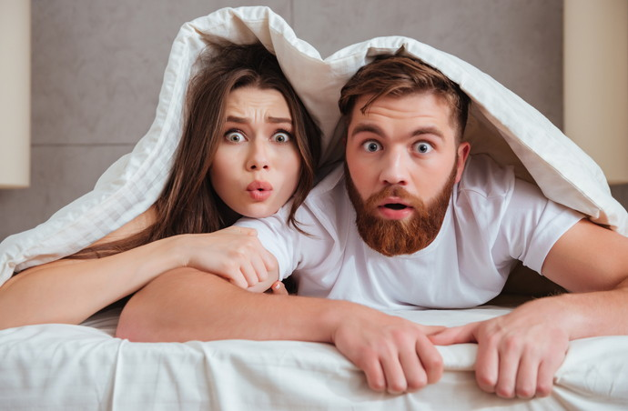 Shocked young loving couple looking at camera while lying in bed under blanket