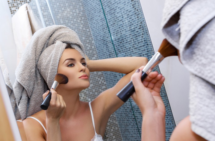 Beautiful woman with a towel on her head, looking in the mirror and applying make up