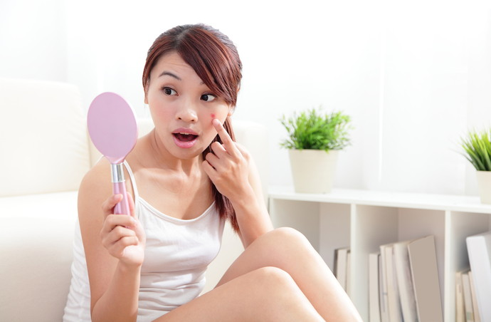 unhappy Woman finding acne on face by mirror at home, asian beauty
